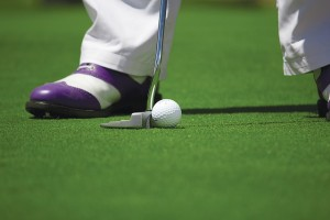 Golfer with purple shoes putting on the green