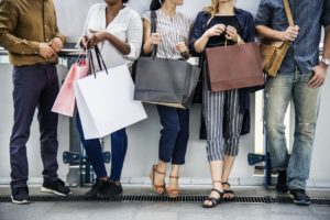 Group of adults chatting while holding shopping bags.