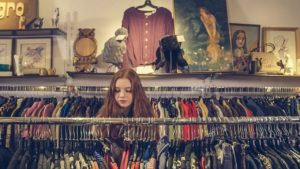 Woman with red hair browsing a rack of clothing for sale in a vintage store.