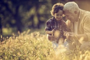 A grandfather playing with his grandson in a field of wheat.