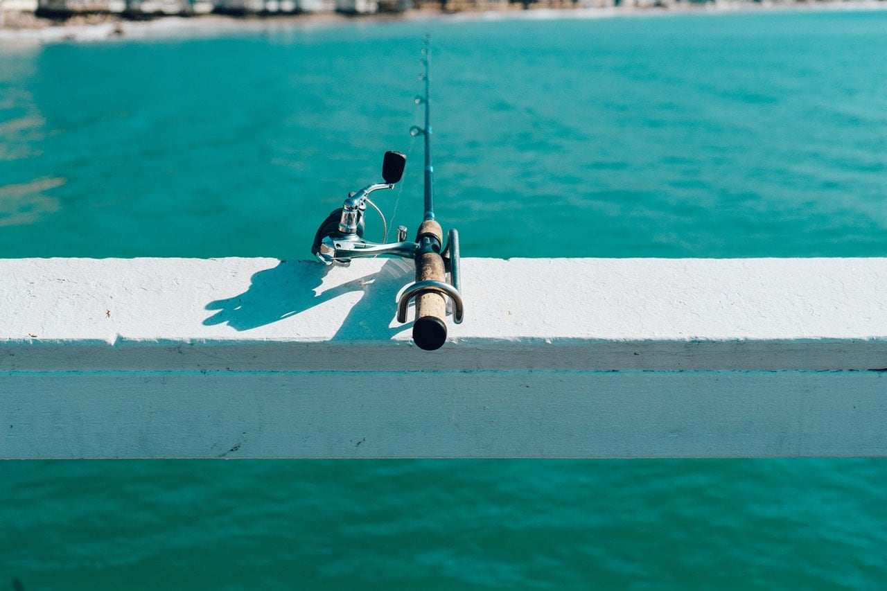 A fishing pole balancing on the side of a boardwalk.