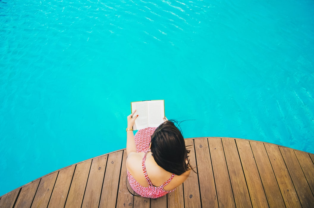 A woman reading by the pool.