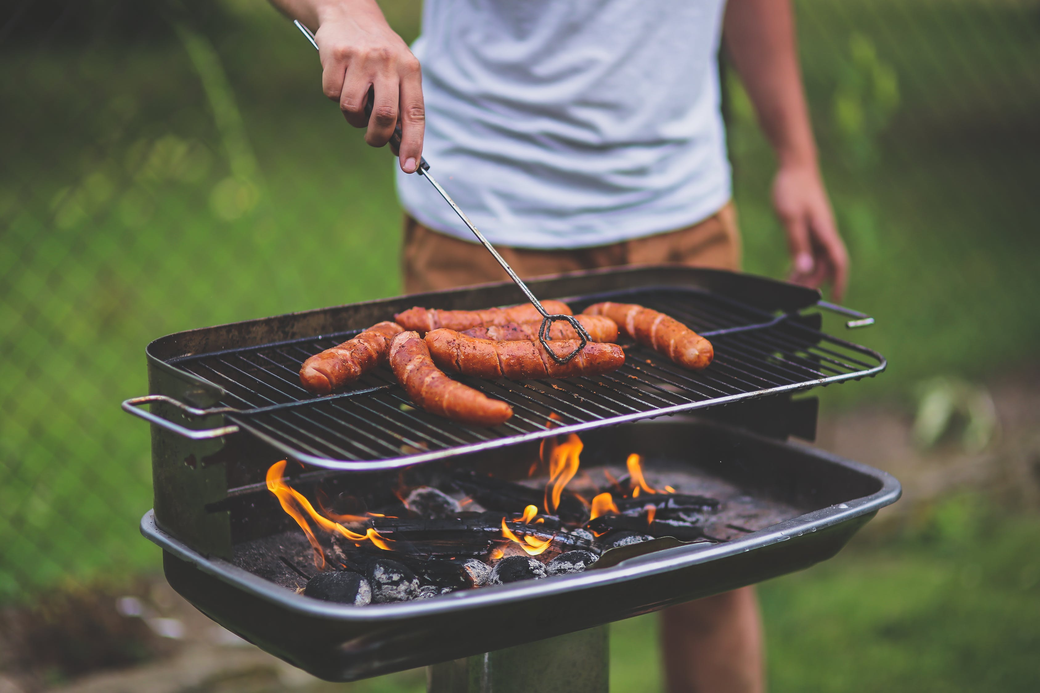 A man grilling hot dogs.